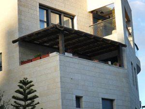 פרגולה גושנית להצללה עם במבוק מושחל במרפסת בבניין דירות וכך נכניס קצת חמימות למבנה האבן הגדול