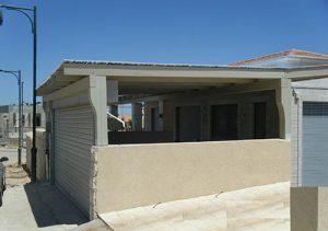 פרגולה גושנית מקורה עם פוליגל לחניה בכניסה לבית עם עמודים גושניים מעוצבים